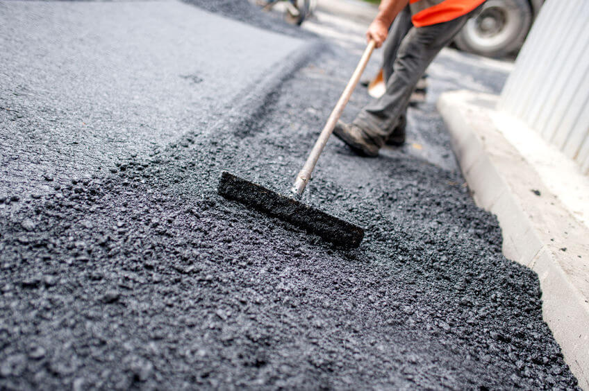 Worker leveling fresh asphalt
